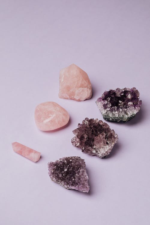 Composition of rose quartz and geode amethyst arranged in rows on gray table