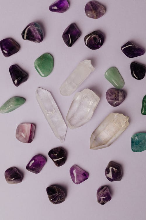 Assorted various crystals and polished semiprecious stones against gray background