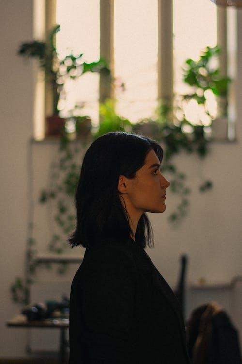 Woman in Black Shirt Standing Near White Wall