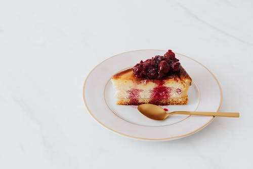 Piece of cheesecake on plate served with spoon
