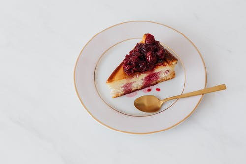 Tasty cheesecake on plate with spoon
