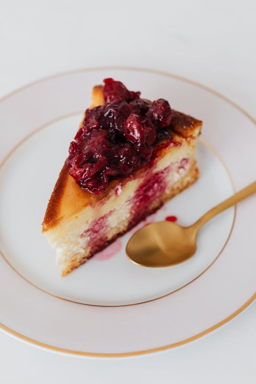 Piece of cheesecake garnished with cherries in syrup