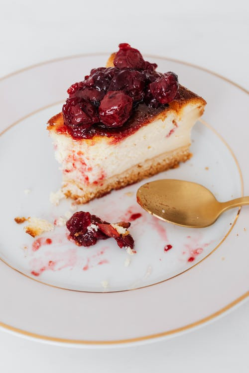 Bitten piece of cherry cheesecake on plate