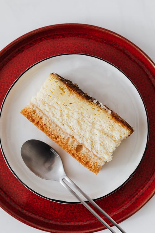 Appetizing dessert on plates with tea spoon