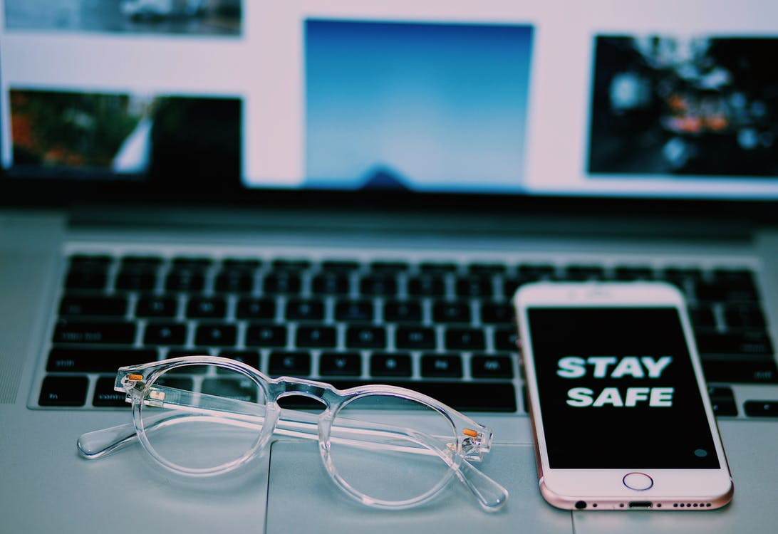 High angle of modern cellphone with Stay safe on screensaver and netbook with glasses placed above