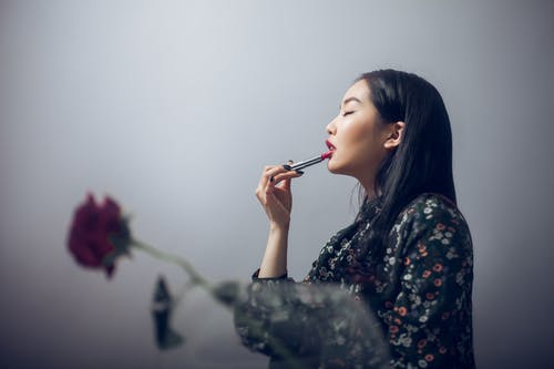 Side view of Asian woman in trendy clothes putting lipstick on lips while standing near rose in vase