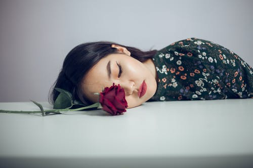 Melancholy ethnic woman with red rose on table