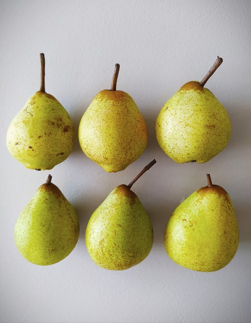 Yellow Pears on White Surface