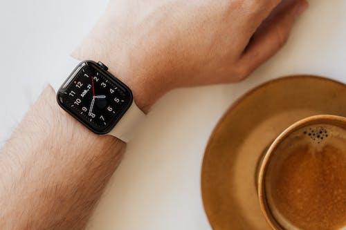 Smart watch on wrist of man drinking coffee