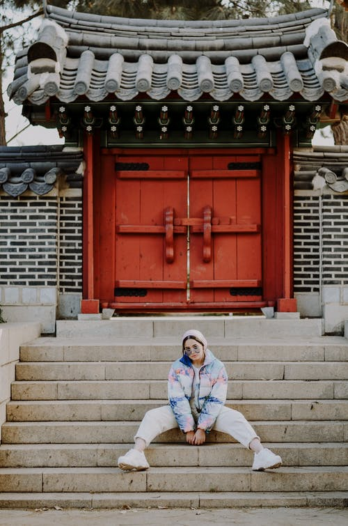 Woman in White and Blue Jacket Sitting on Gray Concrete Stairs