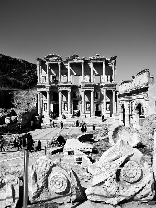 Black and white tourists walking among ancient ruins of the ancient library of Celsus in Ephesus during sightseeing