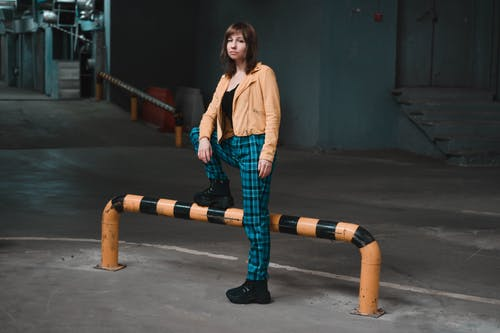 Full length stylish brunette in tartan pants and trendy jacket standing confidently on industrial underground parking