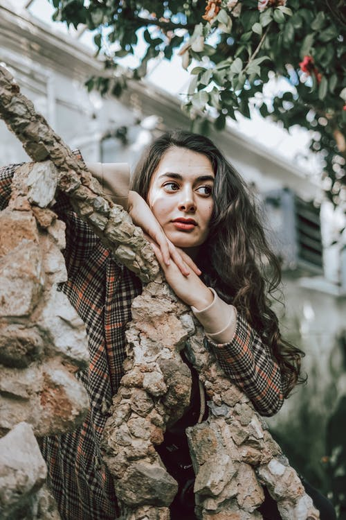 Dreaming brunette in checkered coat leaning on wooden trunk and looking away in hothouse