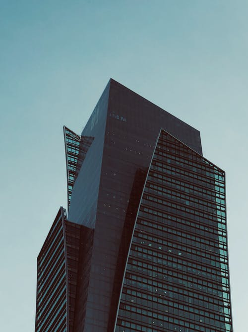 Low angle of contemporary high rise building with black glass exterior under blue clear sky