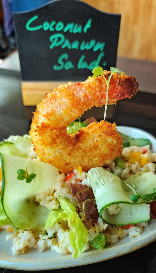 Plate of green salad with coconut fried prawn served on counter with signboard in cafeteria