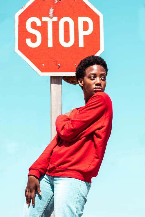 Woman in Red Long Sleeved Shirt Holding Stop Sign