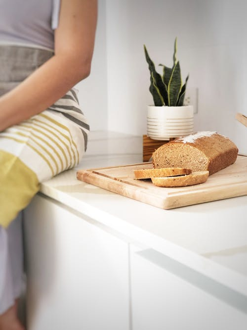 Person in White and Black Stripe Shirt Holding Brown Bread
