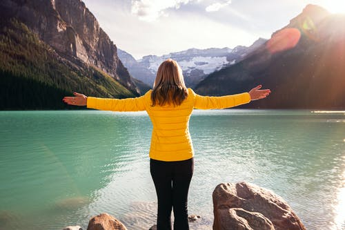Woman in Yellow Long Sleeve Shirt and Black Pants Standing on Rock Near Body of Water