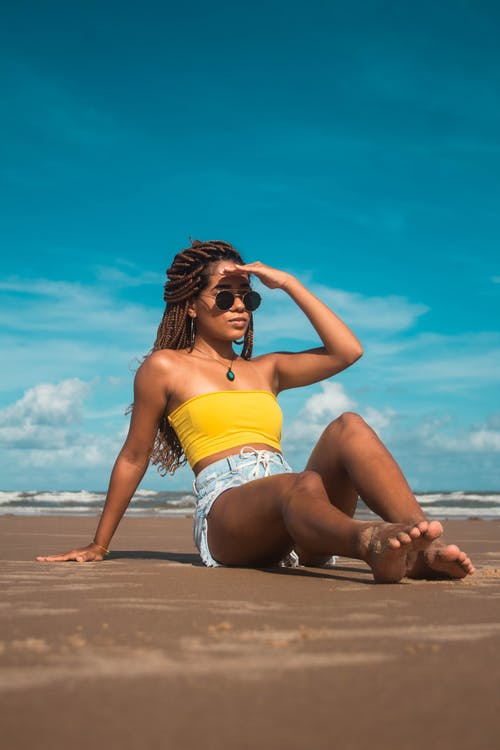 Full body slim woman with dreadlocks chilling on coast and looking away in sunshine