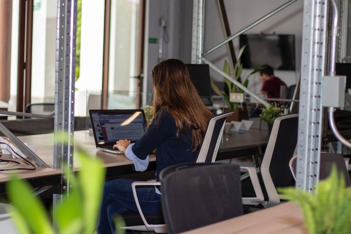 Woman in Black Long Sleeve ShirtUsing A Laptop