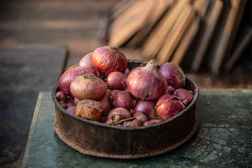Old bowl with pile of red onions on rustic table