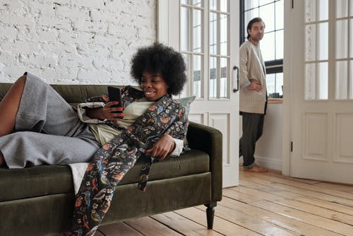 Woman Lying on a Sofa with her Smartphone