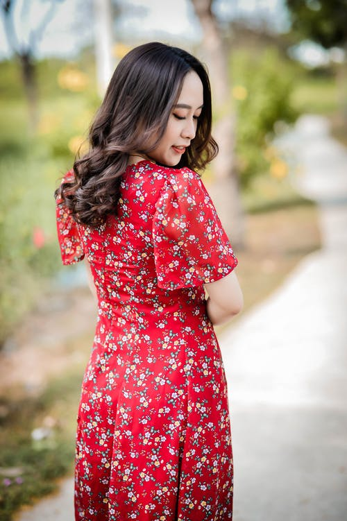 Girl in Red and White Floral Dress Standing on Road