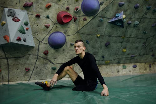 Man Sitting by Climbing Wall