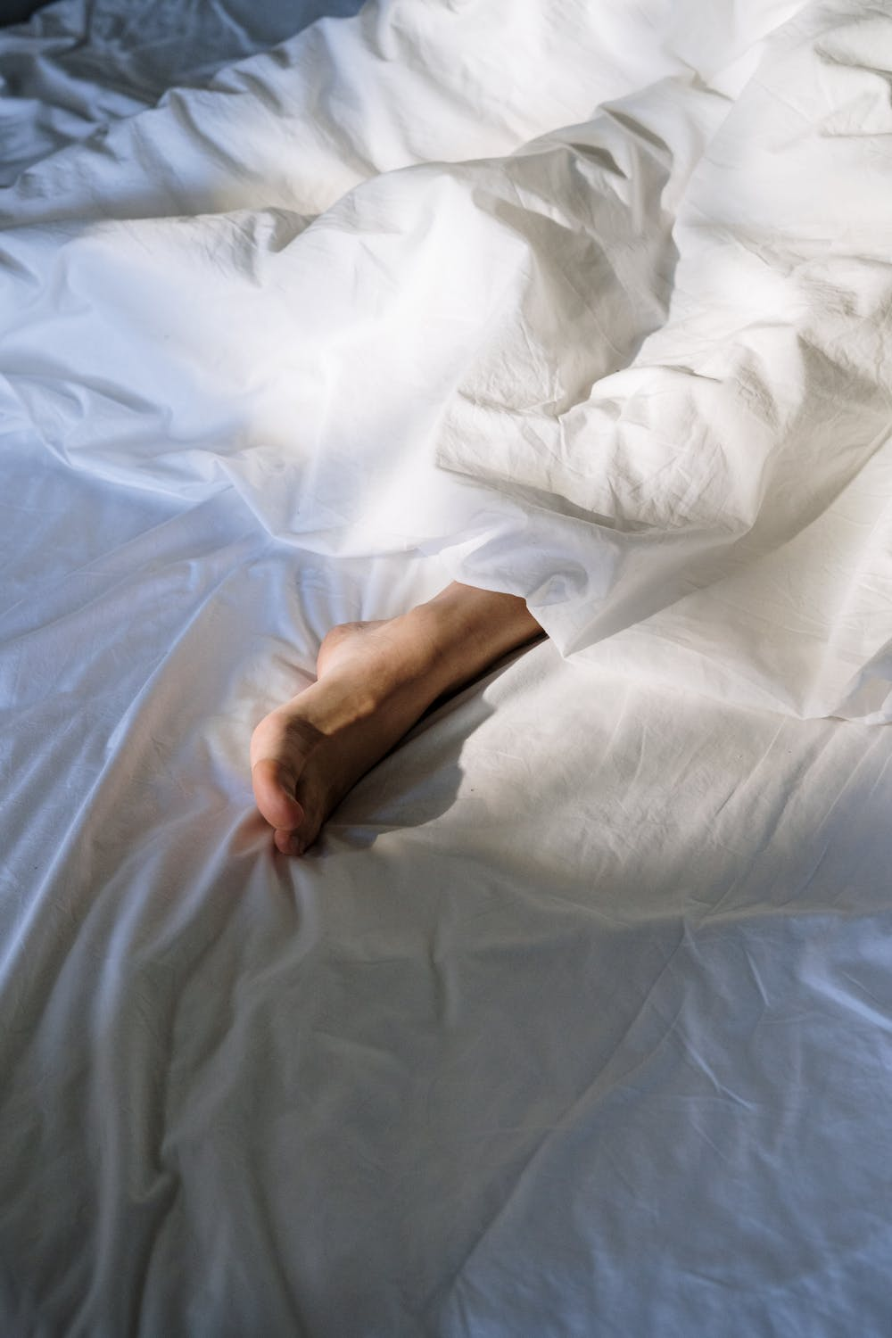foot poking through the blankets in bed