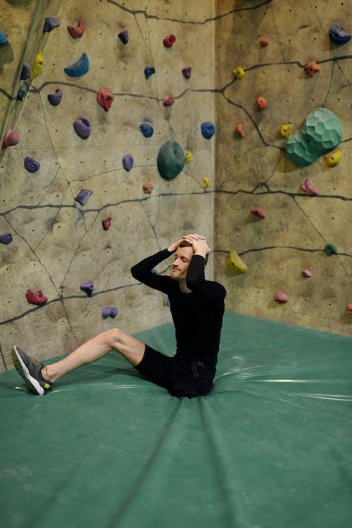 Man Sitting by Climbing Wall