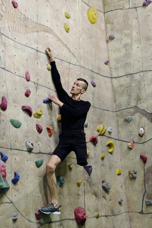 Man in Black T-shirt and Black Shorts Doing Wall Climbing