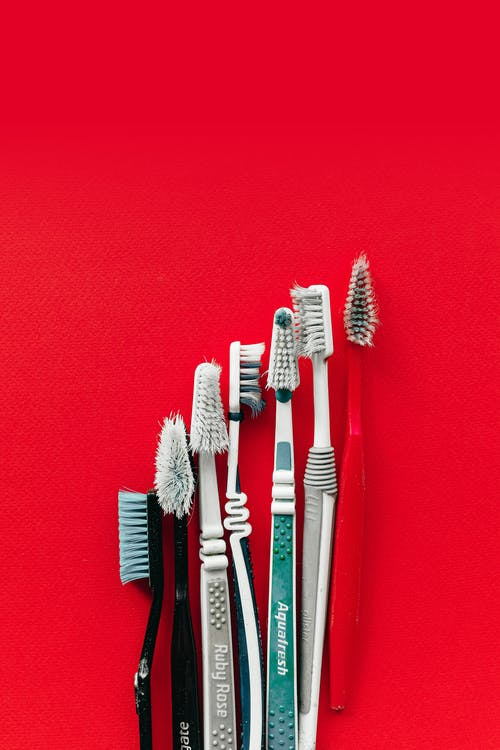 Used Toothbrushes on Red Surface