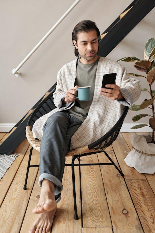 머그잔과 스마트 폰으로 앉아있는 남자