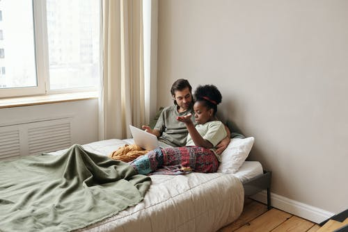 Couple Relaxing In Bed While Using Laptop