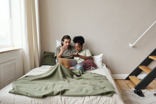 Couple in Bed With a Laptop Arguing