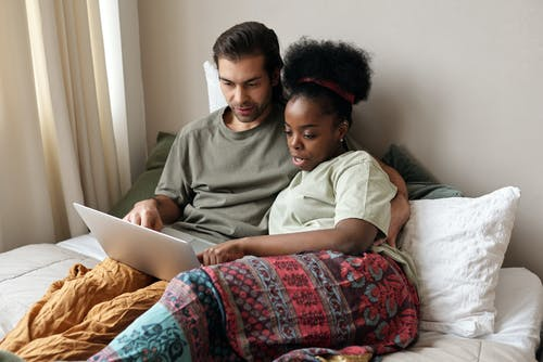 Couple With a Laptop in Bed