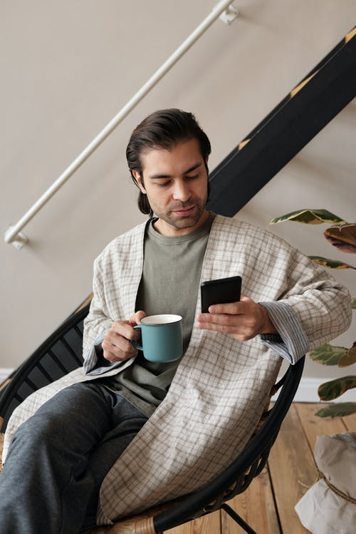 Man Sitting With a Mug and a Smartphone