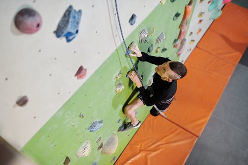 Man in Black Jacket and Black Pants Climbing On Wall