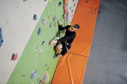 Man in Black Shirt and Black Pants Climbing A Wall