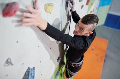 Man in Black Long Sleeve Shirt Doing Wall Climbing