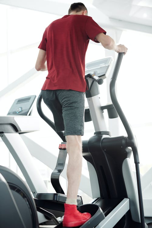 Man in Red T-shirt and Black Shorts Standing on Treadmill