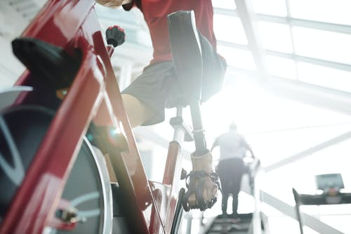 Man in Red T-shirt Riding a Stationary Bike
