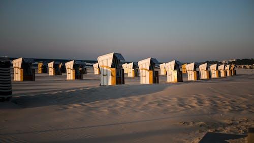 Many similar houses on sandy terrain under blue sky