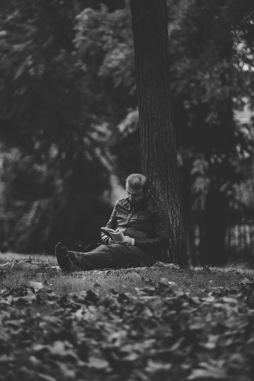 Black and white of anonymous adult male sitting with crossed legs leaned on thick tree trunk while reading textbook near leaves on dry terrain in rural zone