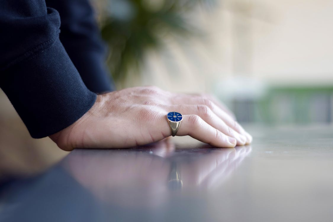 Selective Focus Photo of Person Wearing Blue And Silver Ring