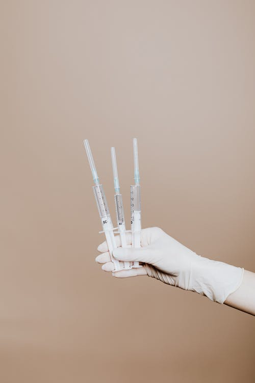 Person Holding Three Syringes with Medicine