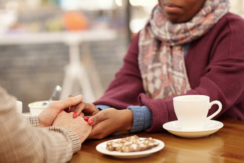 Couple Holding Hands Over Table