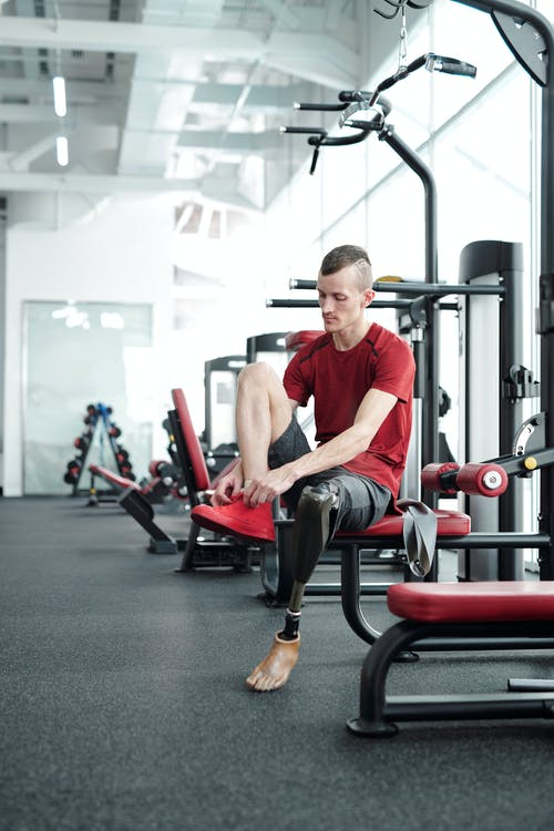 Man in Red Crew Neck T-shirt Sitting on Black and Red Gym Equipment