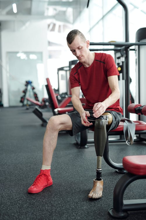 Man in Red Crew Neck T-shirt Sitting on Red and Black Exercise Equipment