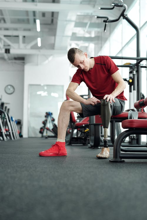 Man in Red T-shirt and Gray Shorts Sitting on Black and Red Exercise Equipment